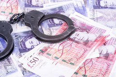 Crime and Money. Handcuffs are on the pounds. Photo showing money with handcuffs Royalty Free Stock Photos