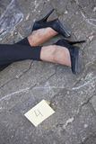 Crime scene. Outline of female legs and placard on the ground Stock Image