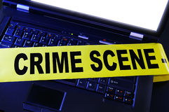 Crime scene. Laptop with yellow crime scene tape across it Royalty Free Stock Photography