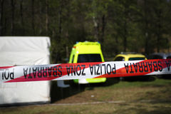 Crime scene background. Red and white police line around a crime scene tent in a forest with ambulance,police and coroner vehicles stock image