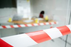 Crime Scene. Blurred shot of crime scene: striped crime scene tape, interior of modern office with desk, chair and marker board on background Stock Photography