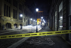 Crime scene investigation. A chalk outline and a yellow police do not cross ribbon at a crime scene in the city during night Royalty Free Stock Photos