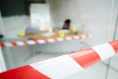 Crime Scene. Close-up shot of striped crime scene tape, interior of modern office with desk, chair and marker board on background Stock Photography