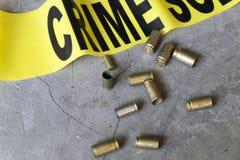 Crime scene close up of crime scene tape and brass bullet casings Stock Photo