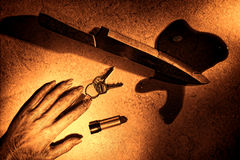 Crime Scene with Dead Woman Hand and Bloody Knife. Gruesome murder crime scene of a dead woman hand and dropped victim set of keys and lipstick tube with bloody Royalty Free Stock Images