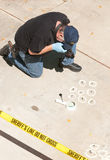 Crime scene detective. Detective studying a crimes scene taking photographs royalty free stock photo
