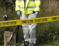 Crime Scene Detective. Detective checking for evidence behind a crime scene barrier Royalty Free Stock Images