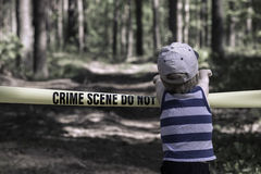Crime Scene Do Not Cross. Little boy in the forest.  royalty free stock photos