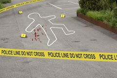 Crime scene, do not cross police tape. Chalk outline circles a human body from a murder