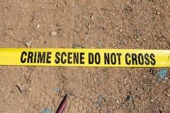 Crime scene do not cross tape on ground Stock Photos
