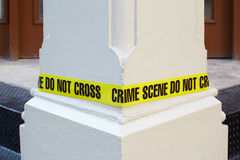 Crime scene do not cross, yellow police tape. Around a white column Stock Image