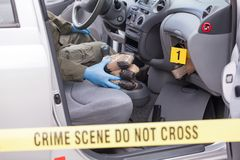 Crime scene: drug smuggling. Police officer holding drug packages found in secret compartment of a car Stock Images