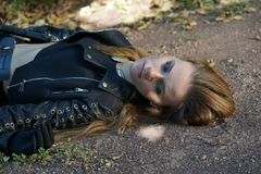 Violent crime. Crime scene - female victim lying dead with open eyes on the ground in an outdoor setting Royalty Free Stock Photo