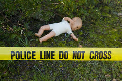 Crime scene in the forest with doll. Crime scene in the forest: Yellow police line do not cross tape and doll royalty free stock images