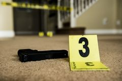 Crime scene. A gun and a crime scene marker on the floor inside a house royalty free stock photo