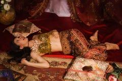 Crime scene imitation: lifeless woman in oriental costume lying Stock Photography