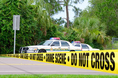 Crime scene investigation. Crime scene photo with crime scene tape crossing a road with Sheriff vehicles parked behind the tape royalty free stock photos