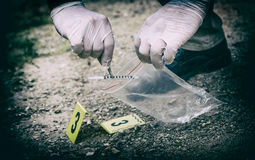 Crime scene investigation. Picking up the tossed syringe and putting it to the plastic bag Stock Photos