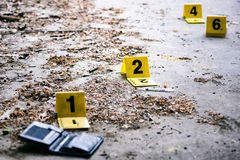 Crime scene investigation. Crime investigation, yellow crime scene marker next to the wallet on the ground royalty free stock images