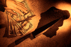 Crime Scene with Money off Dead Man Hand and Knife. Gruesome forensic crime scene of a violent murder with killed dead man hand holding a stack of dollar bills royalty free stock photography
