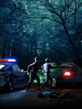 Crime scene. Night scene, with a patrol of two policemen discovering the crime of a young woman in the woods, where a car has been abandoned by the suspect Royalty Free Stock Photography