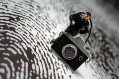 Crime scene photographer. Concept: A man photographs a crime scene with a giant thumbprint representing a crime scene. He is a miniature figurine Royalty Free Stock Photo