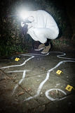 Crime scene photographer. Taking a photo fo during the forensics research of a murder in a park Royalty Free Stock Image
