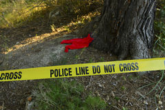 Crime scene: Police line do not cross tape. And romper suit as evidence Royalty Free Stock Photo