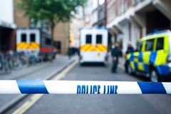 Crime scene with police line tape. Police officers and vans behind safety police line tape Stock Image
