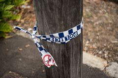 Crime scene police tape tied on wooden pole royalty free stock image