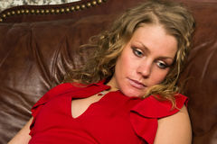 Crime scene simulation: lifeless blonde lying on the sofa. Crime scene simulation: lifeless blonde in the red dress lying on the sofa Stock Photo