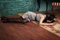 Crime scene simulation: lifeless brunette on the floor stock photo