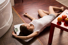 Crime scene simulation. Overdosed girl lying on the floor Royalty Free Stock Image