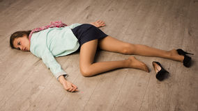 Crime scene simulation. Victim lying on the floor. Crime scene simulation: college girl lying on the floor Royalty Free Stock Image