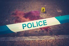 Crime Scene Tape And Blood. A Police Tape Beside The Scene Of A Violent Bloody Crime With Yellow Evidence Marker stock photos