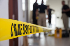 Crime scene tape in building with blurred forensic team backgrou Royalty Free Stock Images