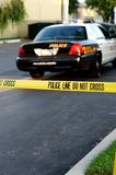 Crime Scene. Tape in the foreground with a blurred police car in the background at a Royalty Free Stock Image