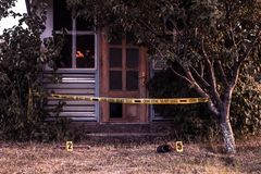 Crime scene tape near the house. Police tape Do Not Cross outdoors royalty free stock photos