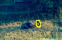 Crime scene, yellow marker evidence, a shoe. Crime scene tape near the house, police tape Do Not Cross outdoors, with axe stock photos