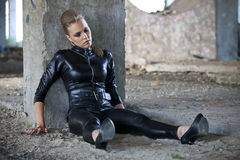 Crime scene. Woman in leather suit sitting unconscious or sleeping on the ground, playing a crime scene Stock Photo