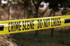 Crime scene yellow police tape closeup. Crime scene tape closeup, police tape Do Not Cross outdoors at investigation royalty free stock photo