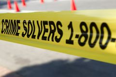 Crime Solvers. Yellow police tape surrounds a crime scene on a street in North America. (Shot with minimum depth of field. Focus is on the first S in Solvers Stock Image