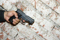 Crime Story Concept. Crime concept. Hand holding a pistol in front of brick wall with harsh shaddow Royalty Free Stock Photos