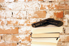 Crime Story Concept. Crime Story: Handgun on top of stack of books in front of old brick wall Royalty Free Stock Images