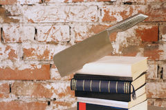Crime Story Concept. Crime Story: Axe shaped knife stuck in books Royalty Free Stock Image