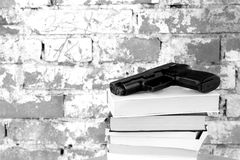 Crime Story Concept. Crime Story: Handgun on top of stack of books in front of old brick wall Royalty Free Stock Photos