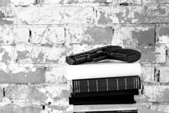 Crime Story Concept. Crime Story: Handgun on top of stack of books in front of old brick wall stock photography