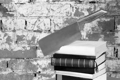 Crime Story Concept. Crime Story: Axe shaped knife stuck in books royalty free stock photos