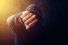 Crime, violence and bullying concept. With hooded criminal person, selective focus on fist Stock Photo
