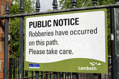 Crime warning sign, Lambeth. LAMBETH, UK - MAY 24, 2014:  A sign fixed to the gate to Kennington Park in Lambeth, South London, warning pedestrians of the threat Royalty Free Stock Image